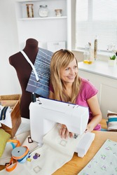 Delighted woman sewing clothes in the kitchen at home