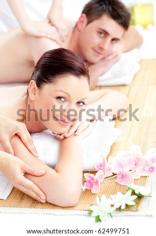 Delighted young couple receiving a back massage in a spa center