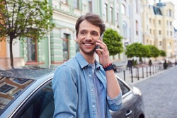 Delighted young male glancing aside while having phone conversation near car