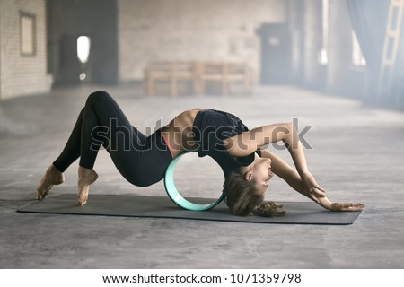 Delightful girl with closed eyes in a black sportswear engaged in yoga in a loft style hall. She does a deflection while lies on the cyan yoga wheel and leans on her toes and head on the mat.