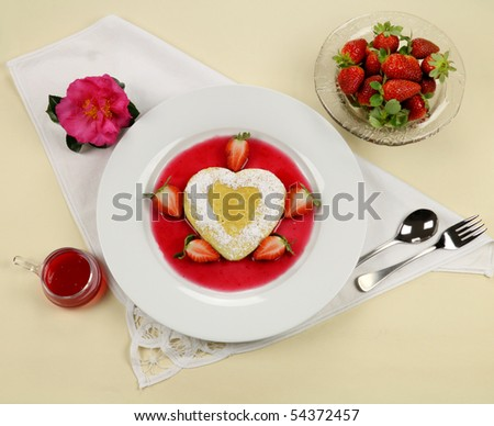 Delightful heart shaped pancake with fresh strawberries and a strawberry sauce.