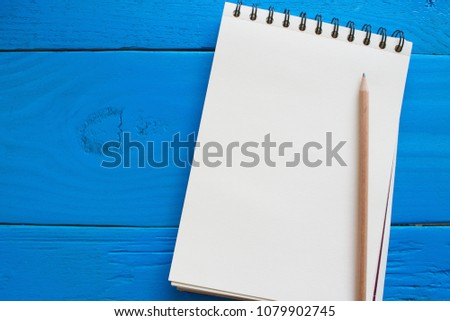 Photo of Delightful image of an empty page of sketch book and a wooden pencil above set on surface of table with a high angle view leaving free space for message