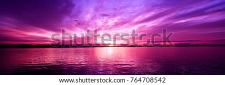 Delightful inspirational magenta coloured cloudy sea water tropical panoramic sunrise seascape featuring wispy cirrus clouds with sparkling ocean water reflections. Australia.