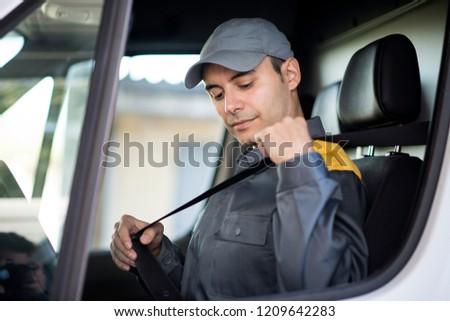 Deliverer putting on the safety belt on his van