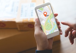 Delivery and online shopping concepts with young person using digital map with smartphone on product package box.Ecommerce market.Transportation logistic.Business retail.