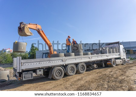 Delivery and unloading of construction materials by the excavator to the construction site. Concrete rings and elements for a well.