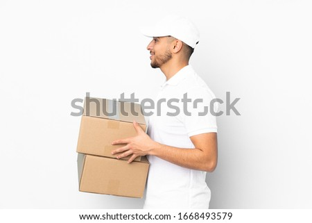 Delivery Arabian man isolated on blue background looking to the side