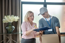 Delivery. Blonde woman in a pink blouse meeting the delivery courrier