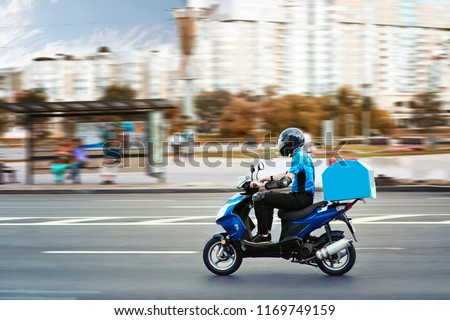 Delivery boy of takeaway on scooter with trunk case box driving fast in rush. Courier delivering food by scooter to avoid traffic jams.