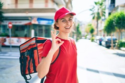 Delivery business worker woman wearing uniform and delivery bag smiling happy doing ok gesture
