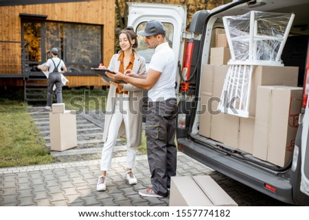 Delivery company employees unloading goods from a car trunk, delivering goods to a woman's home. Happy client signing delivery documents
