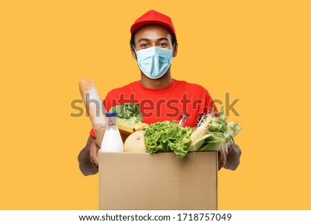 Delivery Concept - Handsome African American delivery man with mask carrying package box of grocery food and drink from store. Isolated on yellow studio Background. Copy Space.