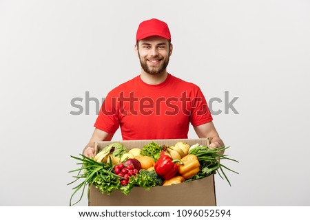 Delivery Concept - Handsome Cacasian delivery man carrying package box of grocery food and drink from store. Isolated on Grey studio Background. Copy Space. #1096052594
