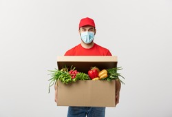 Delivery Concept: Handsome Caucasian grocery delivery courier man in red uniform and face mask with grocery box with fresh fruit and vegetable