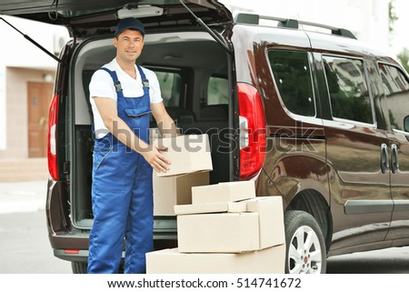 Delivery concept. Postman getting parcels from a car