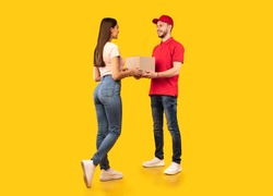 Delivery Courier Guy Giving Parcel Box To Woman Standing Over Yellow Studio Background. Post Packages Delivering, Parcels Transportation Service Concept. Full Length