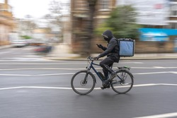 Delivery cyclist riding a bike on a asphalt road with helmet, mask and using a phone. Blurred background.