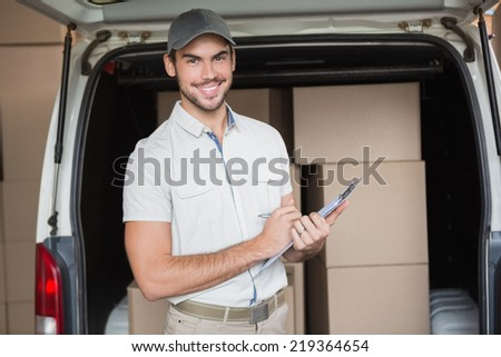 Delivery driver smiling at camera beside his van in a large warehouse