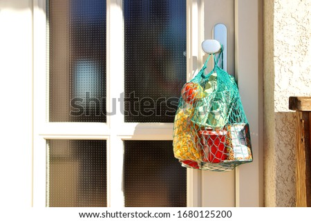 delivery during the quarantine. Shopping bag with Merchandise, goods and food is hanging at the front door, neighborhood Assistance concept at quarantine time because of coronavirus infection Covid-19