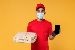 Delivery employee african man in red cap blank print t-shirt face mask gloves work courier service on quarantine coronavirus covid19 virus hold pizza flatbox mobile phone isolated on yellow background