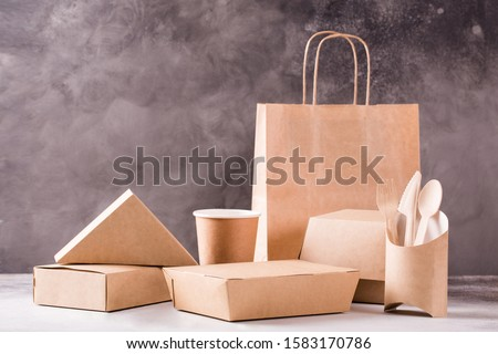 Delivery fast food paper cups, plates and containers. Eco-friendly food packaging and eco bag on gray background with copy space. Food eco packaging made from recycled kraft paper