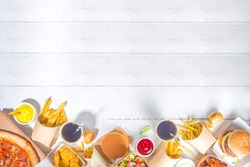 Delivery fastfood ordering food online concept. Large set of assorted take out foods pizza, french fries, fried chicken nuggets, burgers, salads, chicken wings, various sides, white table background