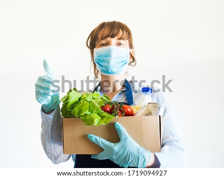 Delivery girl or small shop owner in blue apron with protective face mask holding food delivery box with gloved hands. Safe delivery, grocery shopping concept Photo stock ©