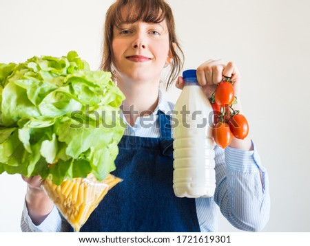 Delivery girl or small shop owner wearing blue apron holding food staples - fresh vegetables, pasta and milk - in gloved hands. Food delivery, grocery shopping Photo stock ©