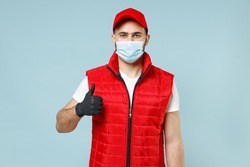 Delivery guy employee man in red cap white t-shirt vest uniform sterile face mask gloves work courier service on lockdown coronavirus flu virus show thumb up gesture isolated on pastel blue background