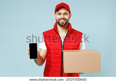 Delivery guy employee man in red cap white T-shirt vest uniform work as dealer courier hold blank cardboard box screen mobile cell phone isolated on pastel blue color background studio Service concept