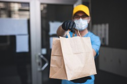 Delivery guy with protective mask and gloves holding box / bag with groceries in front of a building.