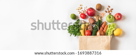 Delivery healthy food background. Vegan vegetarian food in paper bag vegetables and fruits, nuts and grains on white, copy space, banner.Grocery shopping food supermarket and clean eating concept.