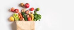 Delivery healthy food background. Vegan vegetarian food in paper bag vegetables and fruits on white, copy space, banner.Grocery shopping food supermarket and clean vegan eating concept.