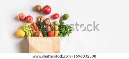 Photo of  Delivery healthy food background. Vegan vegetarian food in paper bag vegetables and fruits on white, copy space, banner.Grocery shopping food supermarket and clean vegan eating concept.