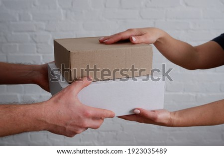 Delivery. Man courier hands over cardboard boxes to woman. Close-up on hands. White brick wall background. Foto stock ©
