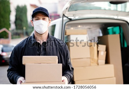 Delivery man courier with face mask delivering parcel boxes in town. Stock photo ©
