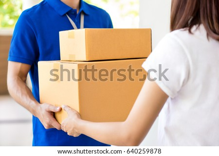 Delivery man delivering parcel boxes to a woman #640259878