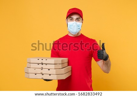 Delivery man employee in red cap t-shirt uniform mask gloves give food order pizza boxes isolated on yellow background studio. Service quarantine pandemic coronavirus virus flu 2019-ncov concept