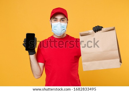 Delivery man employee in red cap t t-shirt uniform mask glove hold craft paper packet cellphone isolated on yellow background studio Service quarantine pandemic coronavirus virus 2019-ncov concept