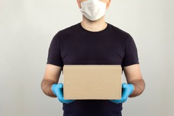 Delivery man holding cardboard boxes in medical rubber gloves and mask. copy space. Fast and free Delivery transport . Online shopping and Express delivery . Quarantine. Mockup