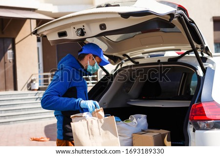 Delivery man holding paper bag with food near the car, food delivery man in protective mask