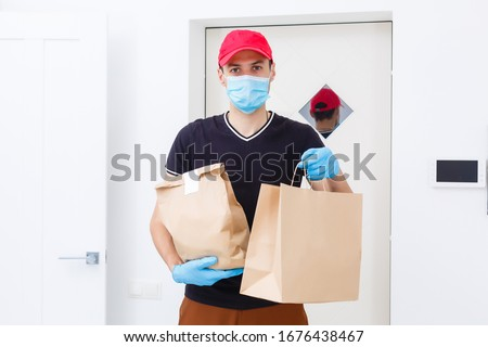 Delivery man holding paper bag with food on white background, food delivery man in protective mask and protective gloves