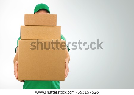 delivery man holding pile of cardboard boxes in front with copy space