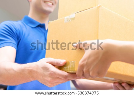 Delivery man in blue uniform handing parcel boxes to recipient - courier service concept