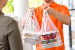 Delivery man in orange uniform delivering Asian food boxes in plastic bags to a woman customer at home
