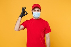 Delivery man in red cap blank t-shirt uniform sterile face mask gloves isolated on yellow background studio Guy employee working courier Service quarantine pandemic coronavirus virus concept
