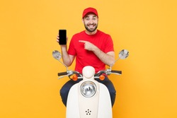 Delivery man in red cap t-shirt uniform driving moped motorbike scooter hold mobile phone isolated on yellow background studio Guy employee working courier Service quarantine pandemic covid19 concept
