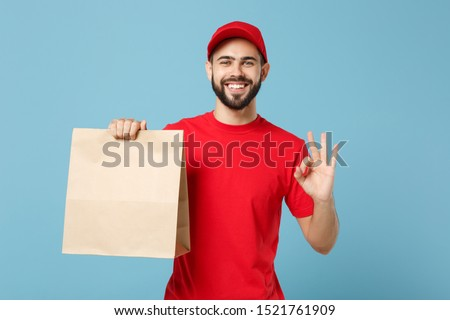 Delivery man in red uniform hold craft paper packet with food isolated on blue background, studio portrait. Male employee in cap t-shirt print working as courier. Service concept. Mock up copy space