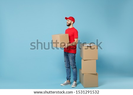 Delivery man in red uniform isolated on blue background, studio portrait. Male employee in cap t-shirt print working as courier dealer hold empty cardboard box. Service concept. Mock up copy space