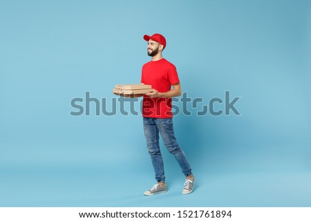 Delivery man in red workwear giving food order pizza boxes isolated on blue background, studio portrait. Professional male employee in cap t-shirt print courier. Service concept. Mock up copy space